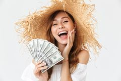 Photo of charming young woman 20s wearing big straw hat rejoicing while holding fan of dollar cash, isolated over white background royalty free stock image