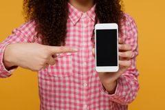 Photo of cheerful cute beautiful young woman chatting by mobile phone isolated over yellow wall background. Looking royalty free stock photos