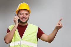Photo of cheerful foreman in yellow helmet talking on walkie-talkie pointing his finger up royalty free stock images