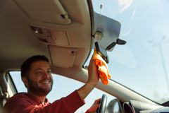 Photo of man with orange rag washing mirror car. Photo of cheerful man with orange rag washing mirror car royalty free stock photography