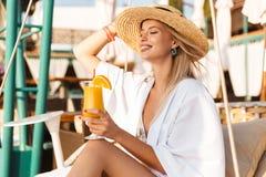 Photo of cheerful stylish woman 20s in straw hat drinking orange Stock Photo