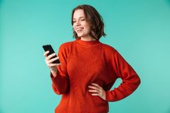 Cheerful woman using mobile phone. Photo of cheerful woman standing isolated over blue background looking aside using mobile phone Royalty Free Stock Photography