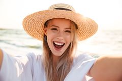 Photo of cheerful young woman 20s in summer straw hat laughing,. Photo of cheerful young woman 20s in summer straw hat laughing and taking selfie while walking Royalty Free Stock Photos