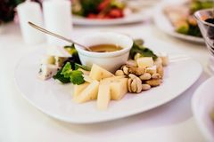 Photo of cheese platter and salad on the table. Cheese platter and salad on the table Royalty Free Stock Image