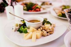 Photo of cheese platter and salad on the table. Cheese platter and salad on the table Royalty Free Stock Photography