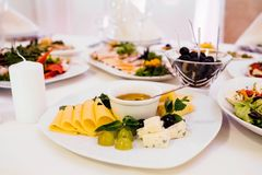 Photo of cheese platter and salad on the table. Cheese platter and salad on the table Stock Photography