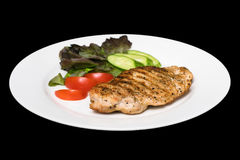 Photo of a chicken stake on a white plate with a cucumber, tomat and a lettuce leaf Royalty Free Stock Photography