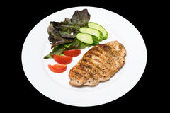 Photo of a chicken stake on a white plate with a cucumber, tomat Royalty Free Stock Photo
