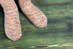 A photo of child feet in knitted stripe socks on the wooden background. Stock Photo