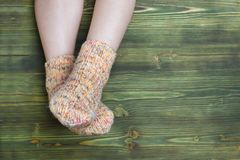 A photo of child feet in knitted stripe socks on the wooden background. Royalty Free Stock Image