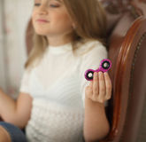 Photo of a child with green and pink fidget spinners in hands, sitting in leather chair, wearing white shirt royalty free stock photos