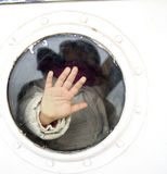 Photo of child hand on a ship window Royalty Free Stock Photo