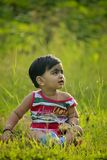 Photo of Child Sitting on Green Grass Field royalty free stock images