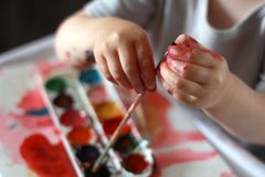 Photo child touches the brush with dirty hands in the paint. against a watercolor paint background. Children`s creativity, painting, early development, fine stock photography
