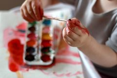 Photo child touches the brush with dirty hands in the paint. against a watercolor paint background. Children`s creativity, painting, early development, fine royalty free stock photo