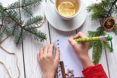 A photo of children`s hands writing in a note book, a cuo of tea anf Christmas decoration. A festive photo of children`s hands writing in a note book, a cuo of Royalty Free Stock Photography
