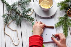 A photo of children`s hands writing in a note book, a cuo of tea anf Christmas decoration. A festive photo of children`s hands writing in a note book, a cuo of Royalty Free Stock Photo