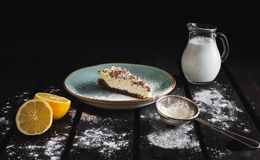 Photo of chocolate bio cheesecake with lemon, milk, caster sugar on wooden background. Dark food Photography of sweet and. Illuminated dessert stock photography