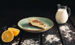 Photo of chocolate bio cheesecake with lemon, milk, caster sugar on wooden background. Dark food Photography of sweet and. Illuminated dessert stock photos