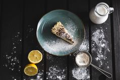 Photo of chocolate cheescake with lemon, milk, caster sugar and sieve on wooden background. Dark food Photography of sweet and. Illuminated dessert from above royalty free stock image