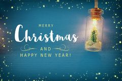 Photo of Christmas tree in the masson jar garland light over wooden blue background. Photo of Christmas tree in the masson jar garland light over wooden blue royalty free stock photography