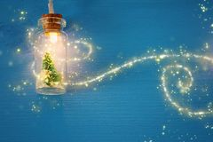 Photo of Christmas tree in the masson jar garland light over wooden blue background. Photo of Christmas tree in the masson jar garland light over wooden blue stock images
