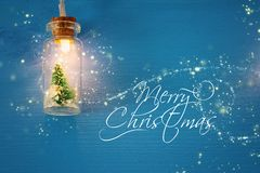 Photo of Christmas tree in the masson jar garland light over wooden blue background. Photo of Christmas tree in the masson jar garland light over wooden blue stock photos