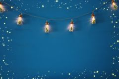 photo of Christmas tree in the masson jar garland lights over wooden blue background. royalty free stock images
