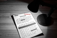 Classified dossier with redactions in a spotlight. Photo of a classified dossier under a spotlight in black and white Stock Image