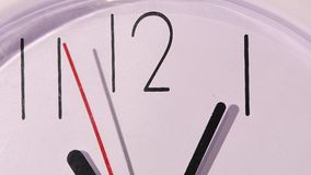 Photo of clock showing several minutes to noon. Close up of an white office clock on colorful background with clipping path stock footage