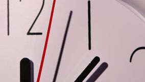 Photo of clock showing several minutes to noon. Close up of an white office clock on colorful background with clipping path. slow motion stock footage