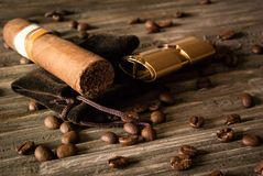 Close-up of cigar and lighter with coffee beans on rough wood. Photo of the close-up of cigar and lighter with coffee beans on rough wood Royalty Free Stock Images