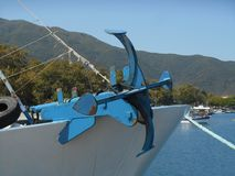 Photo of close up view to reddish and blue anchor standing on front part of fishing boat. Part of sea and mountains, bright blue sky in background, sunny stock photography