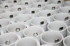 Photo closely standing diagonal rows together 29 white porcelain mugs with stainless steel spoons. Cooking for afternoon tea catering Stock Photo