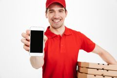 Photo closeup of affable man from delivery service in red t-shir. T and cap holding stack of pizza boxes and showing copyspace screen of cell phone  over white Stock Image