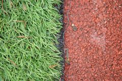 Photo of closeup artificial track and field with green grass combined with artificial grass stock image