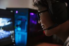 Photo closeup of asian pleased gamer boy playing video games onl. Ine on computer in dark room wearing headphones with microphone and using backlit colorful royalty free stock image