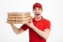Photo closeup of handsome guy from delivery service in red t-shi. Rt and cap holding stack of pizza boxes  over white background Royalty Free Stock Photo