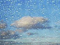 Cloudy blue sky through rainy window stock photography