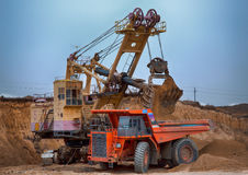 Photo of the coal mine. Autotruck under loading: the excavator loads overburden rock into it. Photo of the coal mine. Machines that work on ledges are well royalty free stock photography