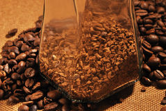 Photo of coffee beans and glass jar with instant coffee on brown background Royalty Free Stock Image