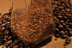 Photo of coffee beans and glass jar with instant coffee on brown background Stock Images