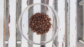 Coffee beans heap in glass heap on wooden table, top view stock photos