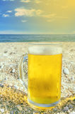 Photo of cold beer bottle in the sand on the beach with burning Stock Images