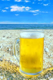Photo of cold beer bottle in the sand on the beach Stock Photo