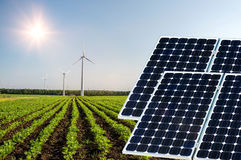Photo collage of solar panels and wind turbins against the crops background Stock Photos