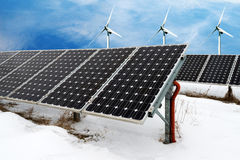 Photo collage of solar panels and wind turbins in winter with snow. Concept of sustainable resources Stock Images