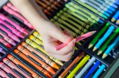 Photo colorée des crayons avec le foyer sur le crayon rose se tenant par l'enfant Image stock