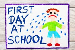 Drawing: Words FIRST DAY AT SCHOOL and sad crying little boy. Photo of  colorful drawing: Words FIRST DAY AT SCHOOL and sad crying little boy Royalty Free Stock Images