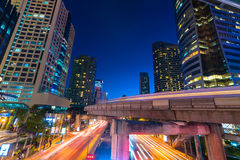 Photo of commercial office buildings exterior. Night view at bot. Tom skyscrapers with light of traffic rush, long exposur in Bangkok Royalty Free Stock Photos